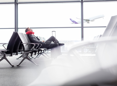 Businessman resting with neck pillow in airport departure areaの写真素材 [FYI02174982]