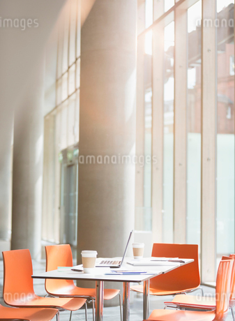 Laptop, coffee and paperwork on table in sunny officeの写真素材 [FYI02175010]