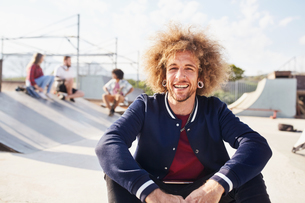 Portrait confident young man with afro at sunny skate parkの写真素材 [FYI02175024]