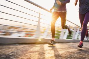 Runner couple running on sunny urban footbridge at sunriseの写真素材 [FYI02175036]