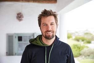 Portrait smiling brunette man wearing hoody on patioの写真素材 [FYI02175039]