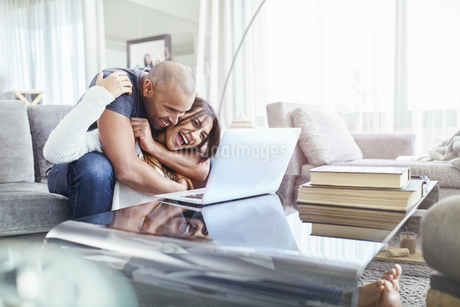 Playful couple hugging and using laptop in living roomの写真素材 [FYI02175042]