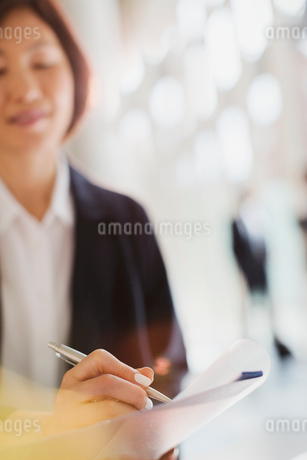 Businesswoman with pen writing on paperworkの写真素材 [FYI02175056]