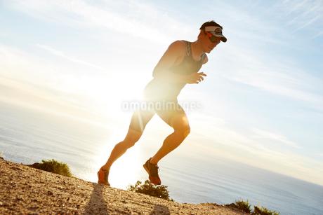 Male triathlete runner running along oceanの写真素材 [FYI02175091]