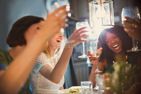 Laughing women friends toasting white wine glasses dining in restaurantの写真素材 [FYI02175097]