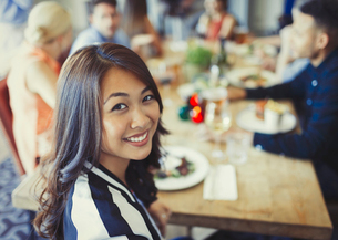 Portrait smiling woman dining with friends at restaurant tableの写真素材 [FYI02175107]