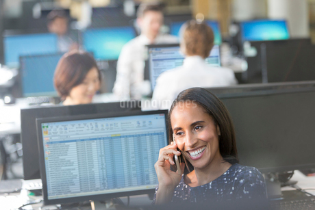 Smiling businesswoman talking on cell phone at computer in officeの写真素材 [FYI02175114]