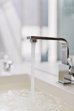 Water from modern faucet filling bathroom sinkの写真素材 [FYI02175131]