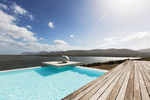 Sunny tranquil modern infinity pool with ocean viewの写真素材 [FYI02175134]