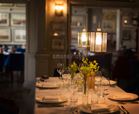 Illuminated pendant lights over placesettings on restaurant tableの写真素材 [FYI02175148]