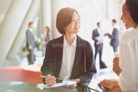 Smiling businesswomen meeting reviewing paperwork in office lobbyの写真素材 [FYI02175153]