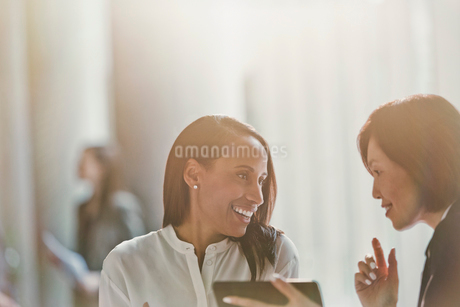 Smiling businesswomen talking, using digital tabletの写真素材 [FYI02175158]
