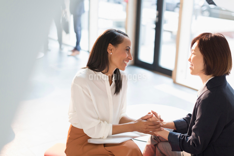 Smiling businesswomen holding hands in sunny office lobbyの写真素材 [FYI02175223]