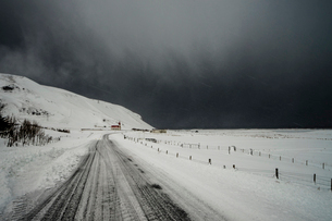 Road through snow covered landscape below stormy sky, Vik, Icelandの写真素材 [FYI02175233]