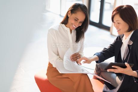 Smiling businesswomen reviewing paperwork in sunny officeの写真素材 [FYI02175245]