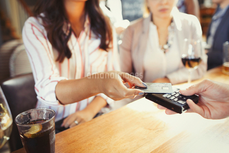 Woman paying bartender with credit card contactless payment at barの写真素材 [FYI02175263]