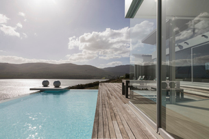 Sunny, tranquil modern luxury home showcase exterior with infinity pool and ocean viewの写真素材 [FYI02175278]