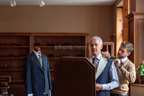 Tailor fitting businessman for suit in menswear shopの写真素材 [FYI02175287]