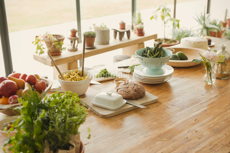 Bread, butter, fruit, pasta,asparagus and fresh herbs on dining room tableの写真素材 [FYI02175292]