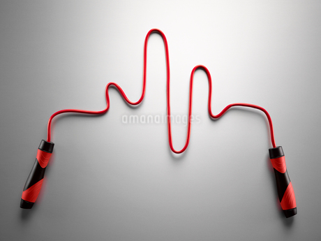 Red jump rope forming pulse trace on gray backgroundの写真素材 [FYI02175309]