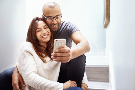 Smiling couple with camera phone taking selfie on stairsの写真素材 [FYI02175313]