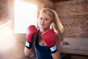 Portrait tough young woman boxing in studioの写真素材 [FYI02175317]