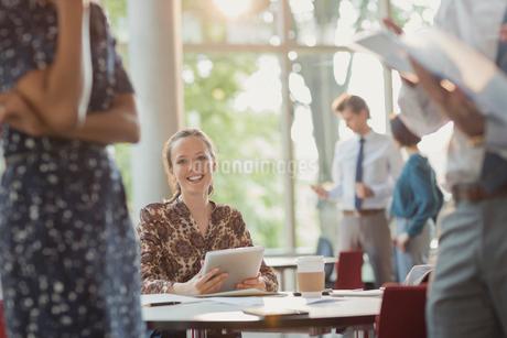 Portrait smiling businesswoman using digital tablet in officeの写真素材 [FYI02175332]