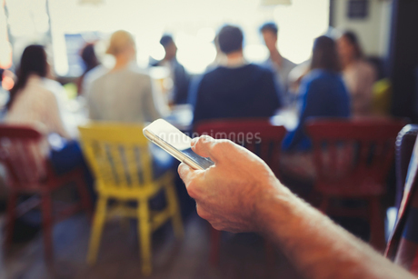 Close up man texting with cell phone in restaurantの写真素材 [FYI02175346]