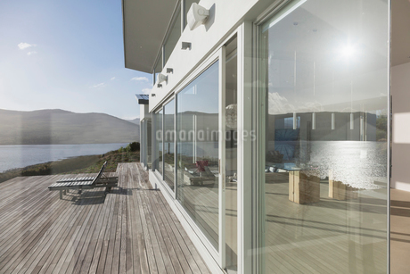 Sunny, tranquil modern luxury home showcase exterior windows and patioの写真素材 [FYI02175380]