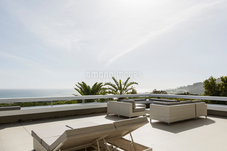Sunny modern luxury patio with lounge chairsの写真素材 [FYI02175397]