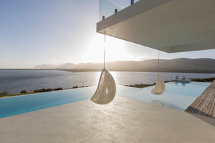 Sunny, tranquil modern luxury home showcase patio with hanging seats and infinity pool with ocean viの写真素材 [FYI02175401]
