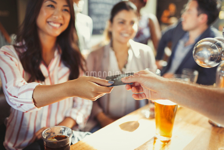 Smiling woman paying bartender with credit card at barの写真素材 [FYI02175418]