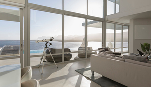 Sunny, tranquil modern luxury home showcase interior living room with telescope and ocean viewの写真素材 [FYI02175427]