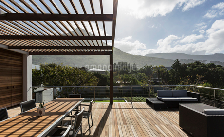 Sunny modern luxury home showcase exterior with wooden deck and mountain viewの写真素材 [FYI02175429]