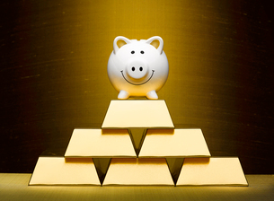 Smiling piggy bank on top of stacked gold barsの写真素材 [FYI02175468]