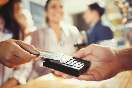 Woman with credit card paying bartender with contactless payment at barの写真素材 [FYI02175486]