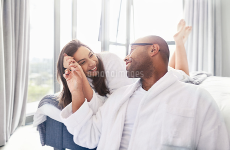 Affectionate couple holding hands in bedroomの写真素材 [FYI02175520]