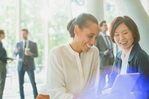 Businesswomen using digital tablet in office lobbyの写真素材 [FYI02175531]