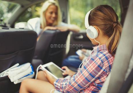 Girl with headphones using digital tablet watching video in back seat of carの写真素材 [FYI02175541]