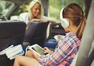 Girl with headphones using digital tablet watching video in back seat of carの写真素材 [FYI02175541]
