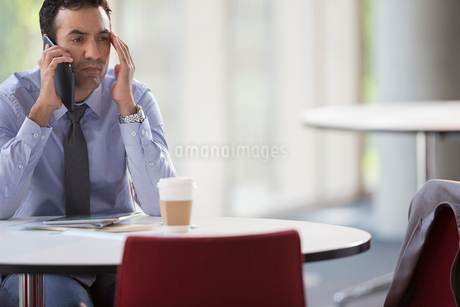 Stressed businessman talking on cell phone at tableの写真素材 [FYI02175550]