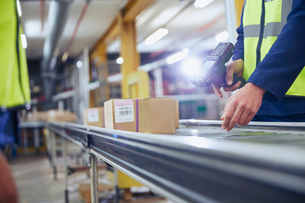 Worker scanning and processing boxes on conveyor belt in distribution warehouseの写真素材 [FYI02175554]