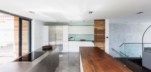 Modern, minimalist home showcase interior kitchen with wood and stainless steel countersの写真素材 [FYI02175566]
