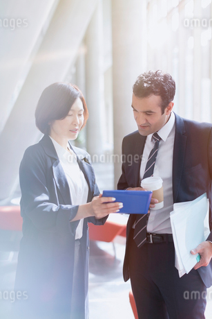 Business people using digital tablet in sunny office lobbyの写真素材 [FYI02175618]