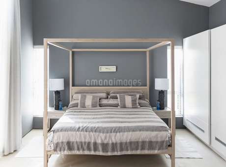 Striped bedding on canopy bed in modern home showcase interior bedroomの写真素材 [FYI02175691]