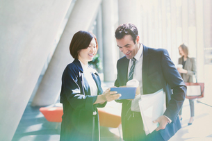 Businessman and businesswoman reviewing paperwork in sunny office lobbyの写真素材 [FYI02175718]