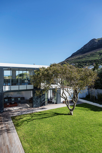 Sunny luxury home showcase exterior and yard below mountainの写真素材 [FYI02175739]