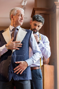 Tailor fitting businessman for suit in menswear shopの写真素材 [FYI02175775]