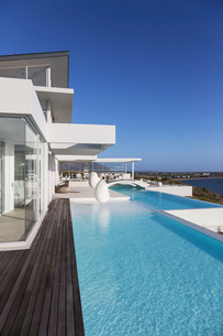 Sunny, tranquil modern luxury home showcase exterior with infinity poolの写真素材 [FYI02175799]