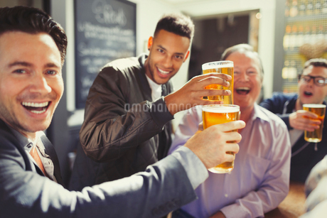 Enthusiastic men friends toasting beer glasses at barの写真素材 [FYI02175800]
